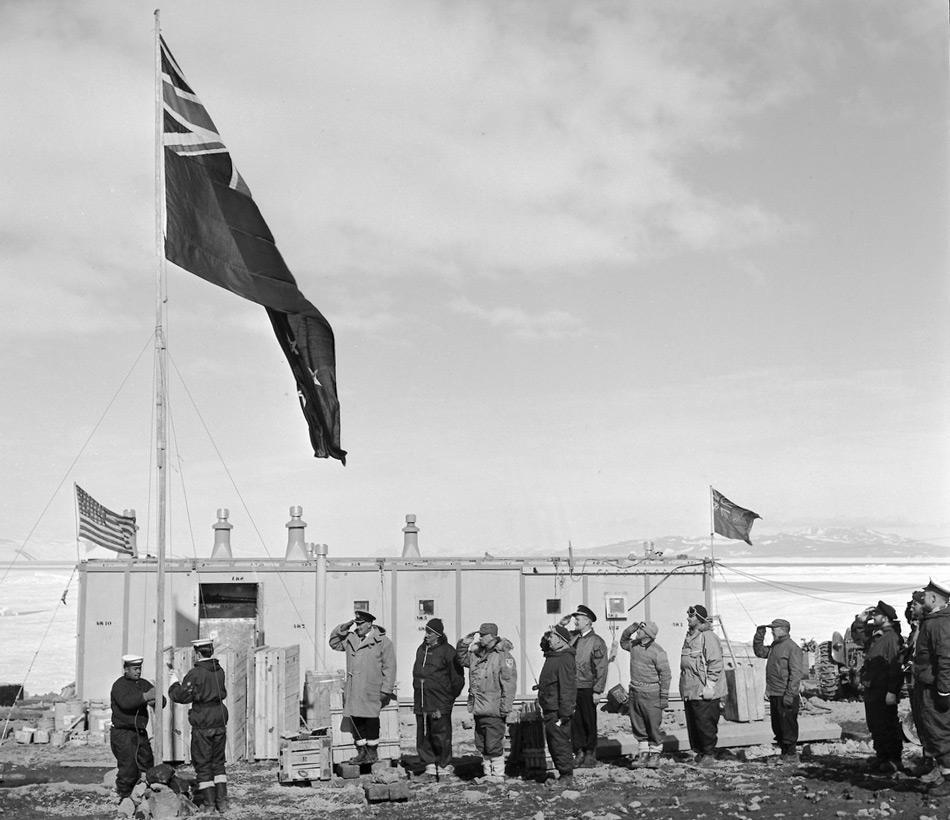 Hissen der neuseeländischen Flagge an Scott Base am 20. Januar 1957 vor der TAE-Hütte. Zeugen sind Mitglieder der neuseeländischen und amerikanischen Antarktis-Expeditionen. (Foto: John Claydon)