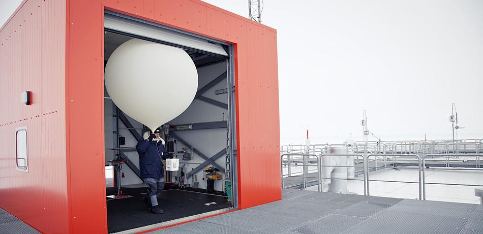 Mit dem Ballon und der Ozonsonde in der Hand geht der Meteorologe, hier Jölund Asseng aus dem Überwinterungsteam 2011, auf das Dach der Neumayer-Station.