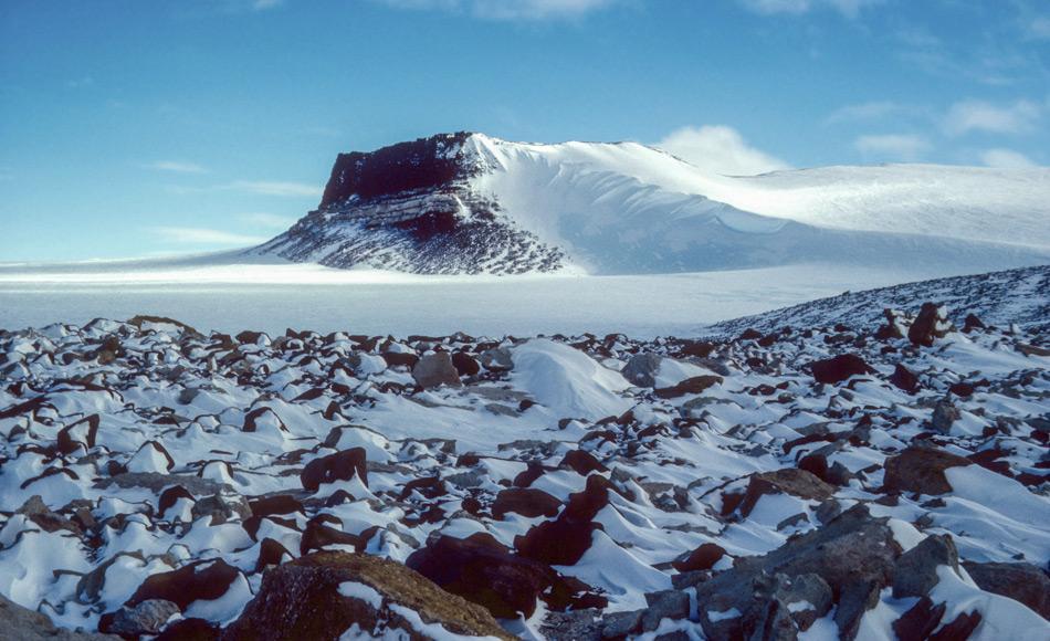 Die Siriusformation, in der sich marine Fossilien finden, ist in der Nähe von Mt. Fleming in der Antarktis exponiert. Das Muster im Schnee hinter den Felsen zeigt die vorherrschende Windrichtung über dem ostantarktischen Eisschild. Bild: Reed Scherer, 1986, Northern Illinois University