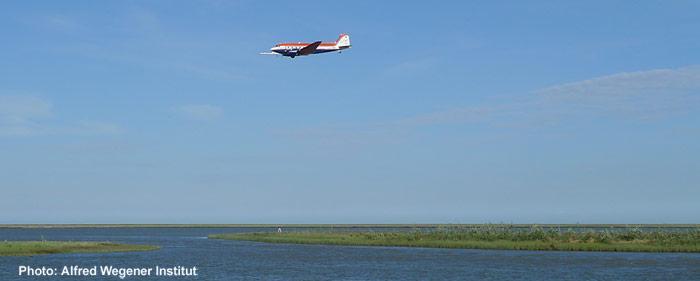 Das Forschungsflugzeug des AWI Polar 5 beim Messflug in der Nähe eines Camps des Geological Survey of Canada.