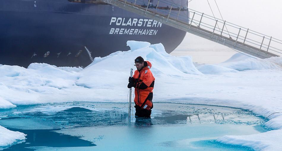 Der Meereisphysiker Dr. Marcel Nicolaus vermisst während der Polarstern-Expedition ARK-XXVII-3 auf einer Eisscholle die Tiefe eines Schmelzwassertümpels. Foto: Stefan Hendricks, AWI